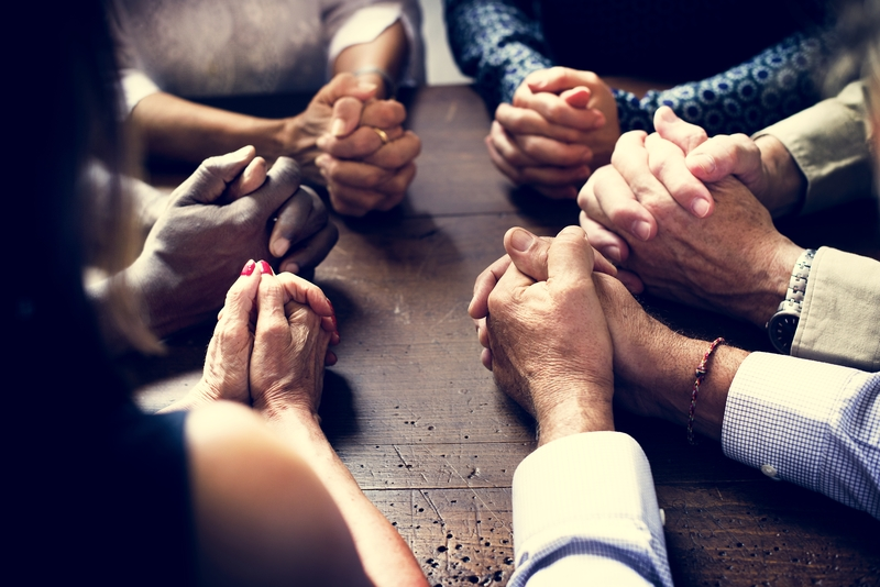 hands-folded-in-community